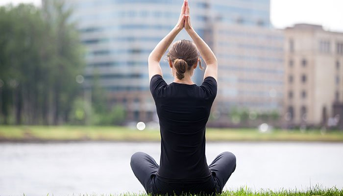 Woman doing yoga in front of an office building