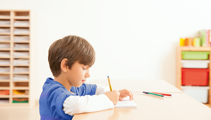 A boy writing with a pencil and paper