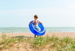 300x205_boy on beach with blue rubber ring