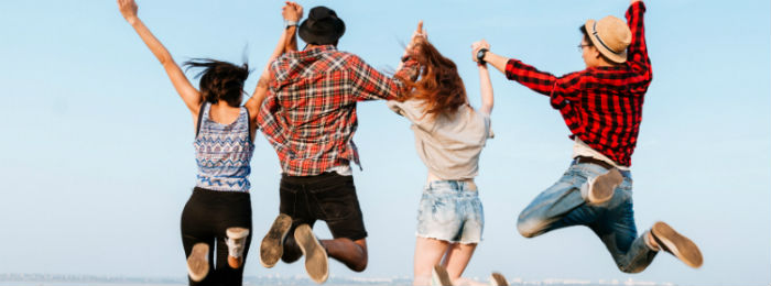 a group of young people holding hands jumping in the air