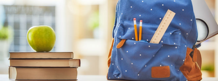 Blue school bag beside pile of books and an apple
