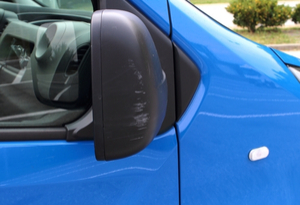 blue van with damage to its wing mirror